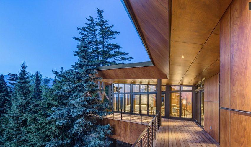 Фасадные панели с имитацией дерева органично вписывают загородный дом в лесной ландшафт
