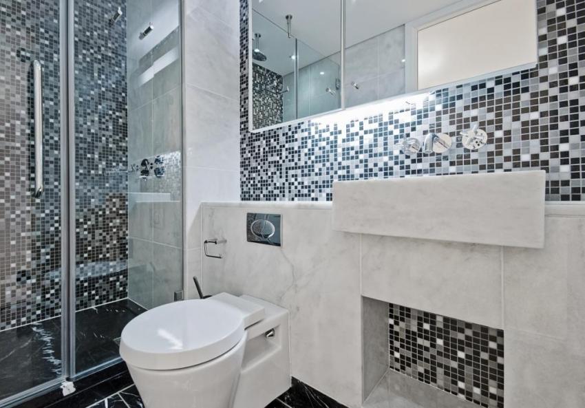 Для оформления ванной небольшого размера стоит использовать мелкую плитку в виде мозаики, подчеркнуть которую можно с помощью зеркальных элементов