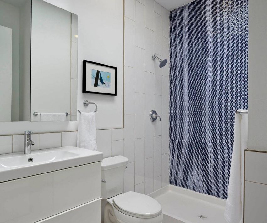 С помощью укладки плитки контрастного цвета на одну из стен можно зрительно углубить пространство ванной комнаты
