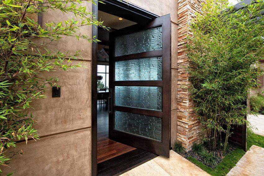 Строгий стиль оформления входной деревянной двери со вставками из прочного стекла