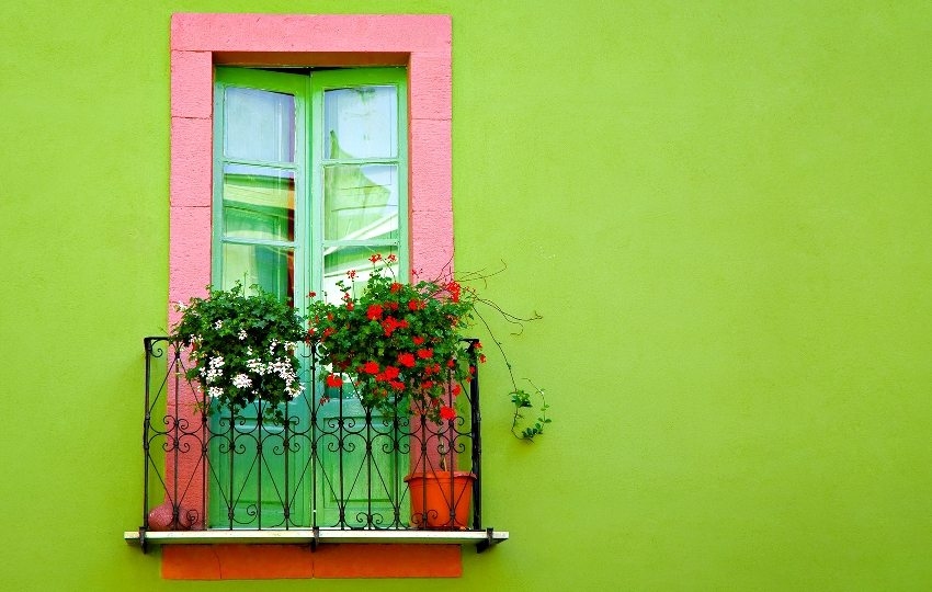 Фасад дома окрашен в яркий салатовый цвет