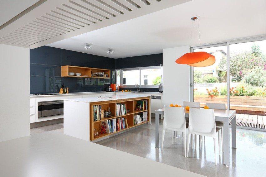 Кухонный фартук оформлен глянцевой прямоугольной плиткой темно-синего цвета