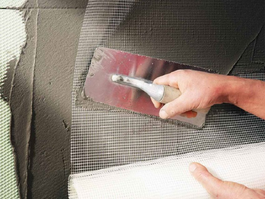 Перед нанесением штукатурки на пенопласт наклеивают армирующую сетку