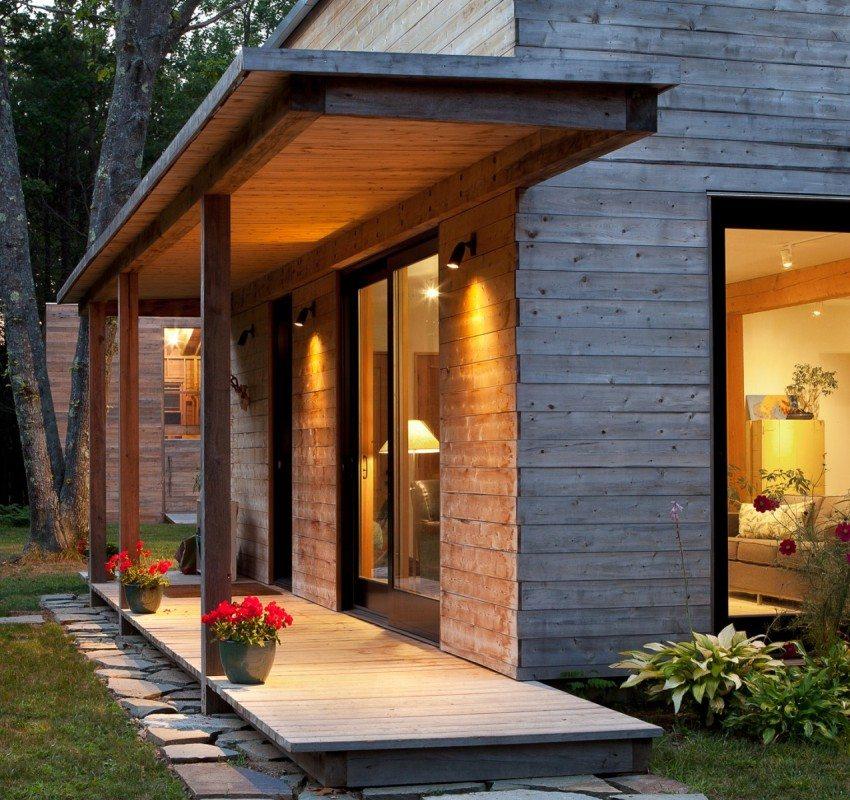 Крыльцо деревянного дома расположено вдоль стены