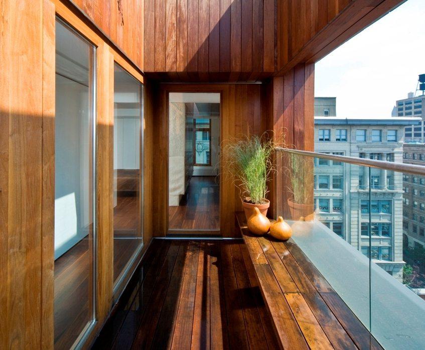 На стенах и полу балкона используется отделка ламинатом