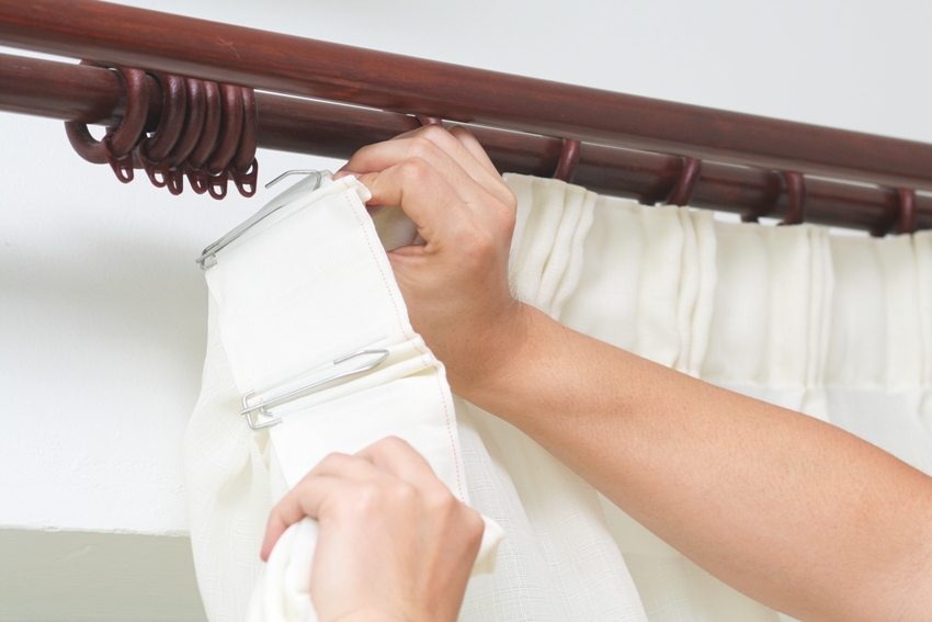 Подвешивание шторы на карнизные держатели с помощью металлических крючков