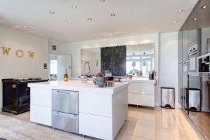Глянцевая плитка на полу и зеркальный фартук визуально расширяют пространство кухни