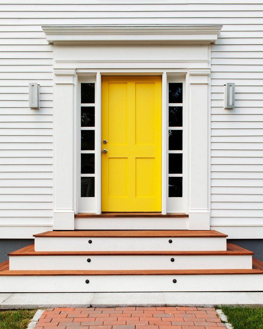 Ярко-жёлтая входная дверь на белом фасаде дома