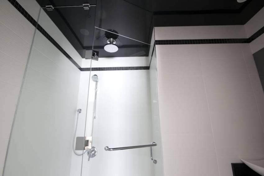 Черный глянцевый потолок красиво смотрится в сочетании с белой керамической плиткой