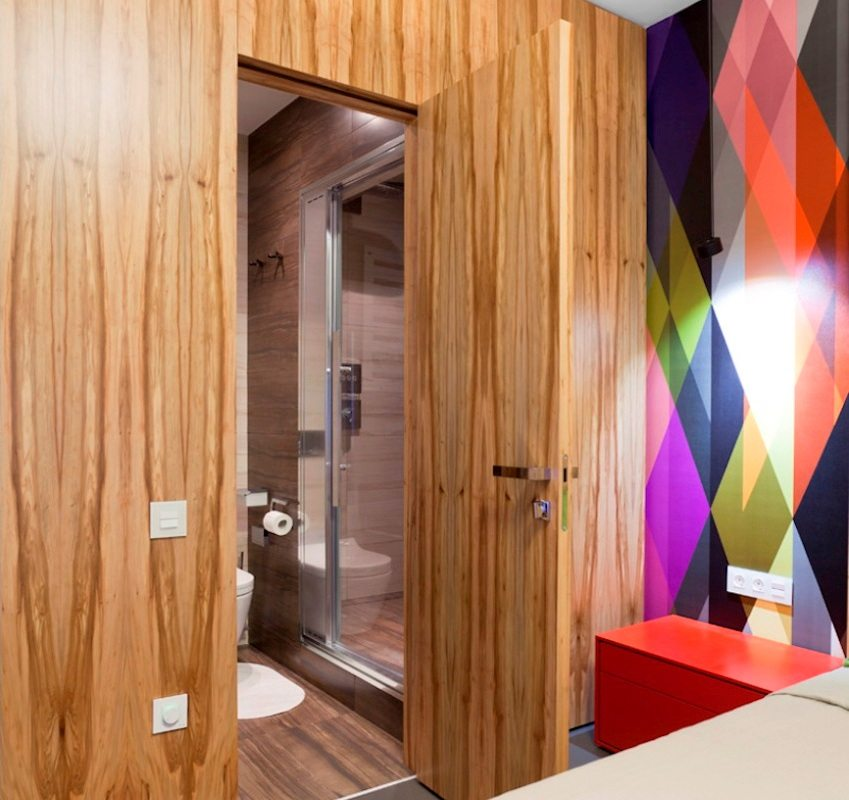 Дверь и стена в спальне облицованы одинаковым деревянным шпоном