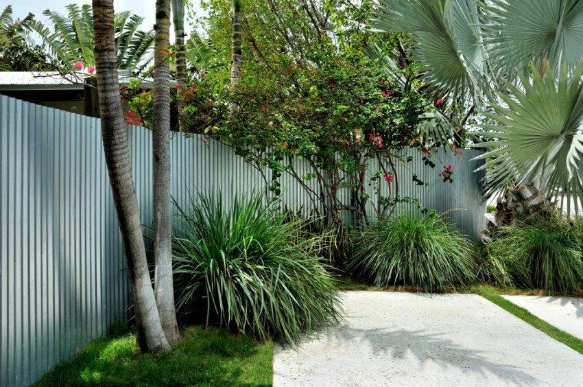 Двор огражден забором из профнастила серого цвета