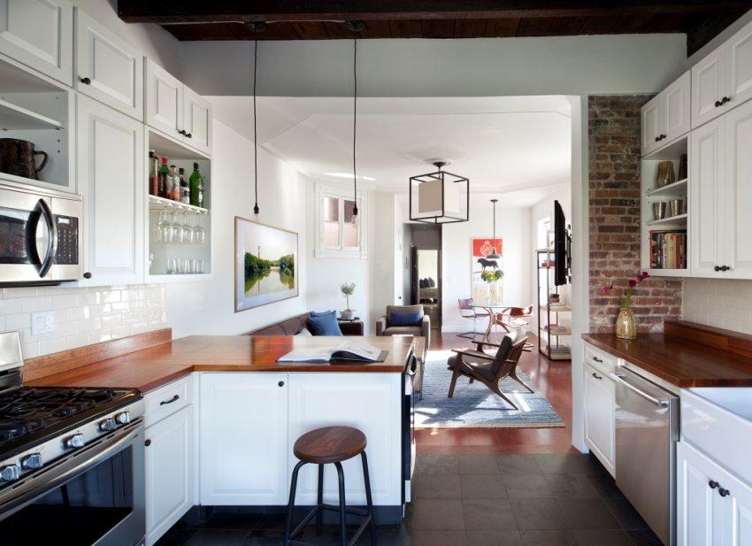 Кухня отделена от гостиной частью стеновой перегородки и Г-образной тумбой