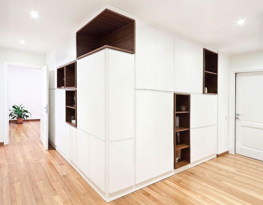 Вдоль стен углового коридора в квартире расположены вместительные шкафы