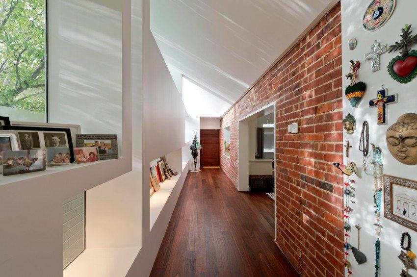 Одна из стен длинного коридора облицована декоративным кирпичом