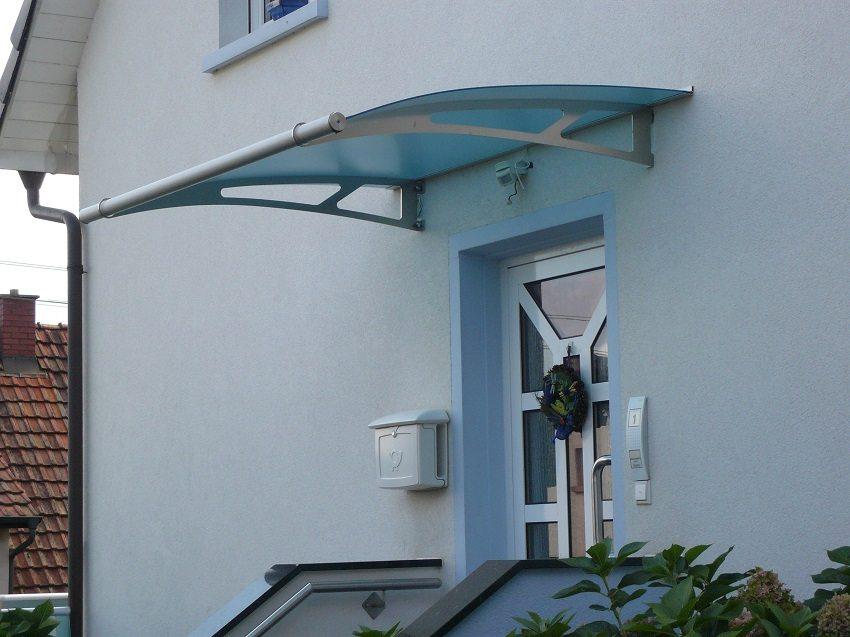 Козырёк из голубого поликарбоната в сочетании с алюминием удачно вписывается в стилистику дома