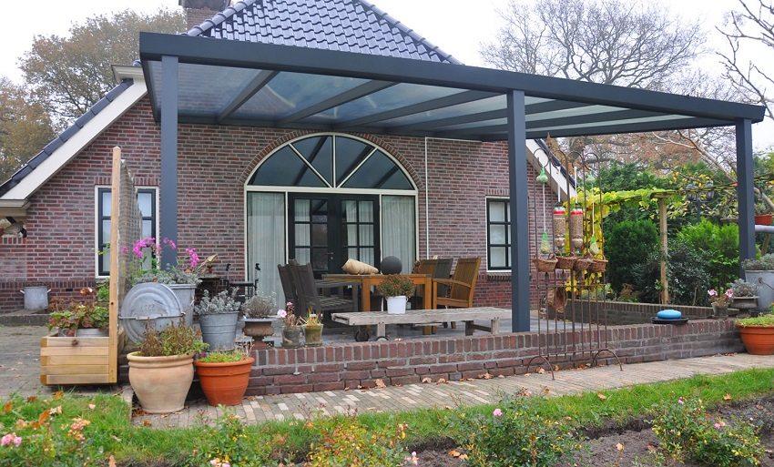 Вход в дом оформлен широким козырьком-навесом из листового поликарбоната