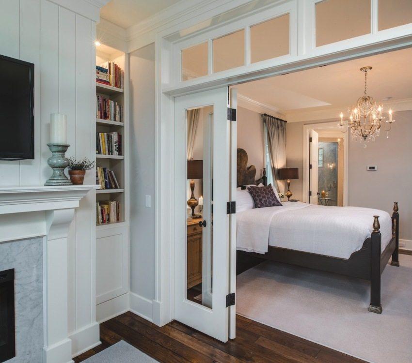 Дверь-гармошка в спальне выполнена из дерева и стекла