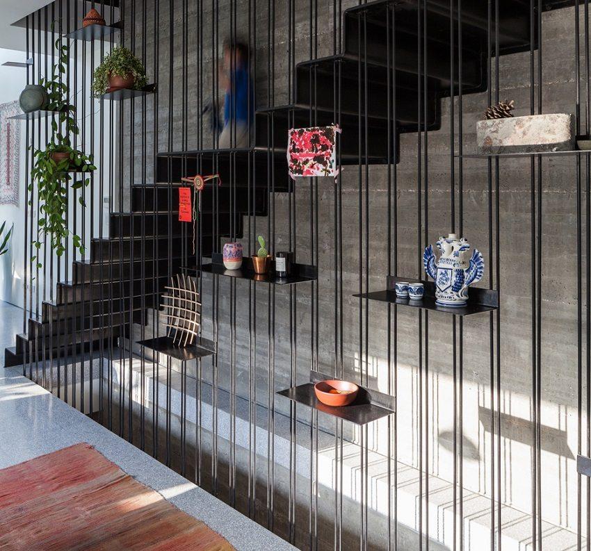 Пристенная металлическая лестница ограждена декоративной завесой из металлического прута с полками для декора