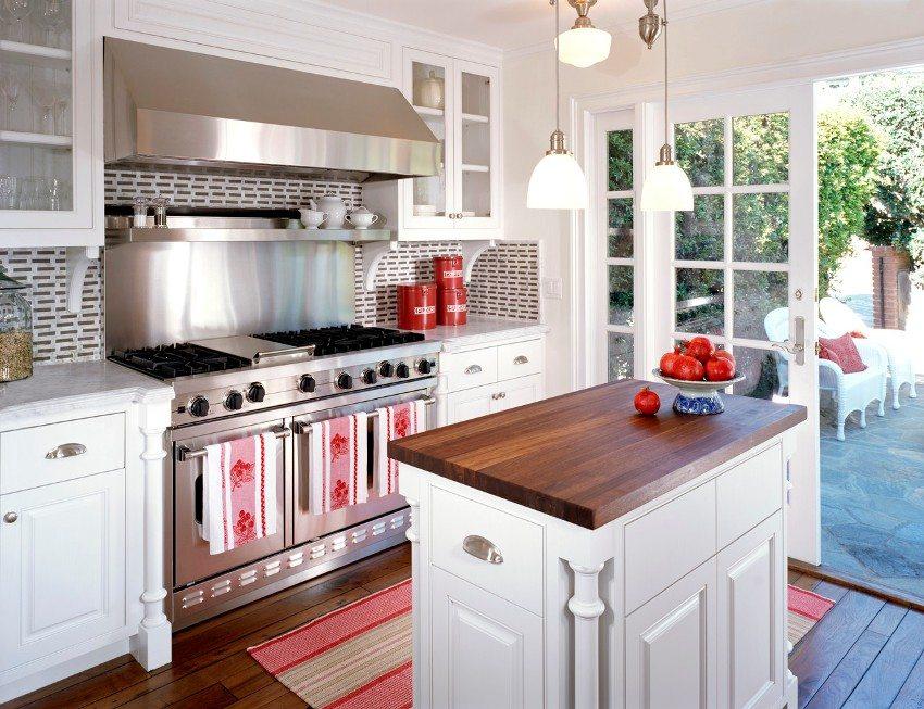 Одна из стен летней кухни оборудована широкими распашными дверями
