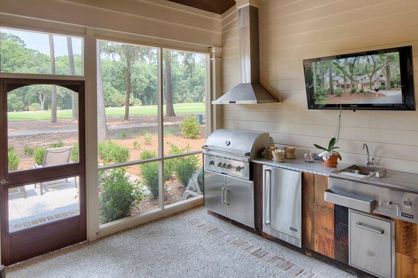 Стеклянная стена летней кухни позволяет закрытому помещению не терять связь с природой