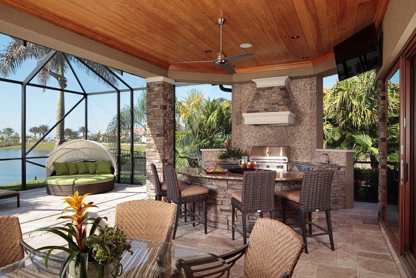 Открытая летняя кухня построена с использованием кирпича, камня и дерева