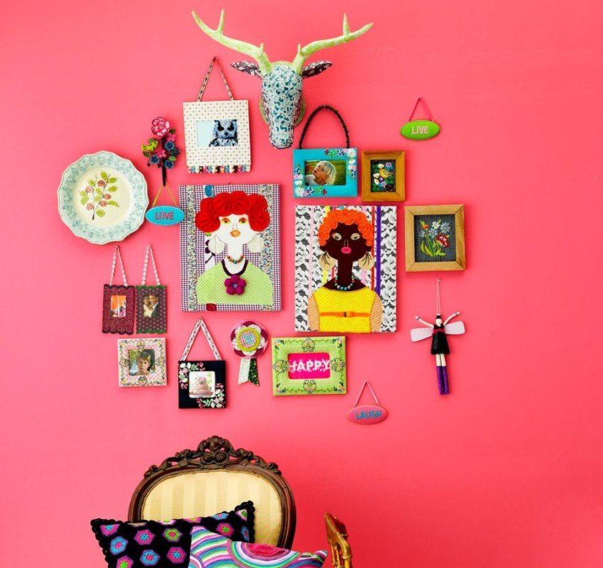 На ярко-розовой стене размещены рамки с фотографиями и рисунками