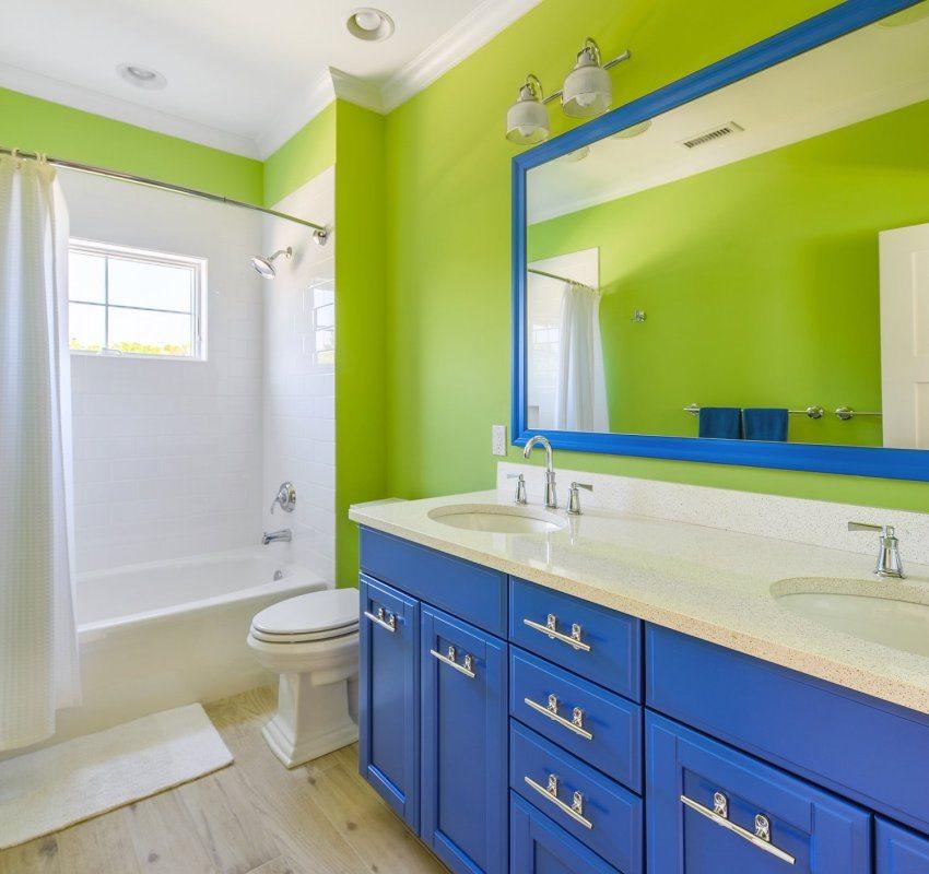 Ярко-салатовые стены ванной комнаты хорошо сочетаются с белой плиткой и контрастной мебелью