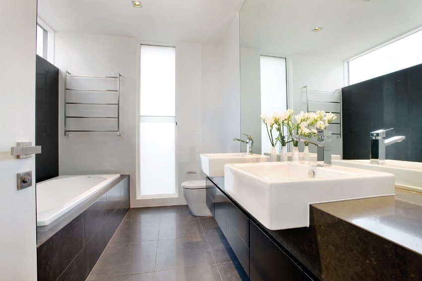 Белые стены ванной комнаты в сочетании с темной плиткой и мебелью