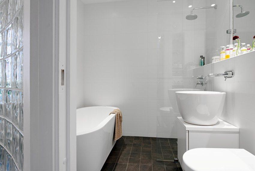 Белая глянцевая плитка на стенах ванной комнаты создает ощущение чистоты и простора