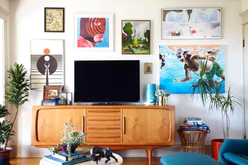 Тумбочка с телевизором в окружении ярких картин и постеров