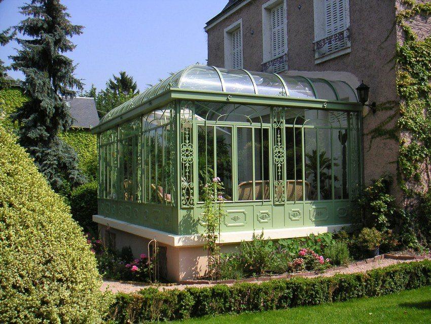 Закрытая веранда, выполненная из металла и стекла, с крышей из поликарбоната