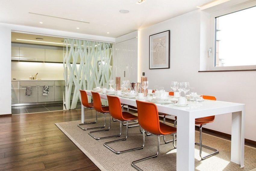 Монохромная гамма кухонной зоны разбавлена контрастными стульями за обеденным столом