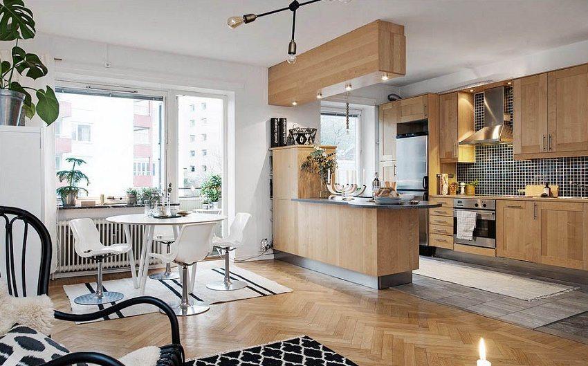 Современная кухня-студия, в дизайне которой сочетается блеск металла с натуральностью дерева