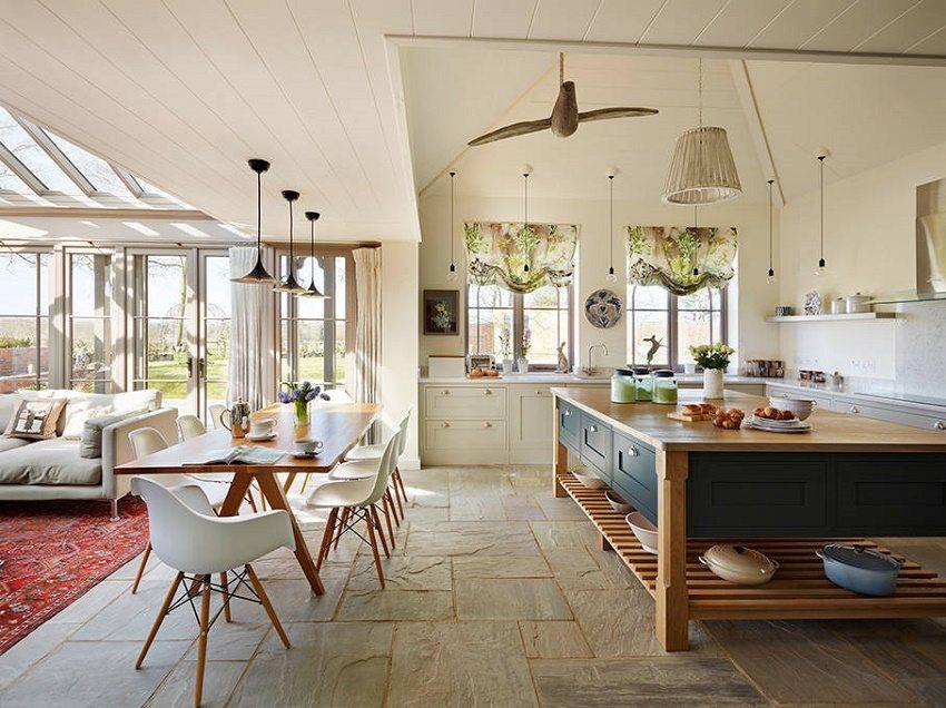 Светлая кухня с большим обеденным столом и функциональным освещением