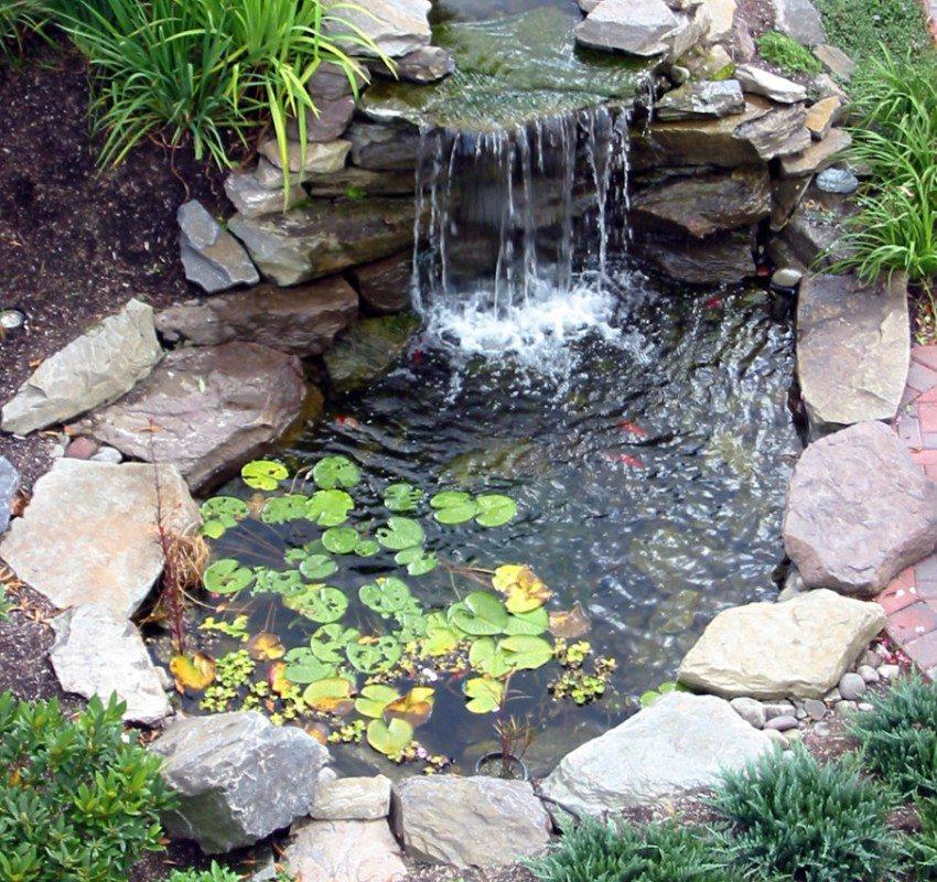 Маленький пруд с водопадом оформлен камнями