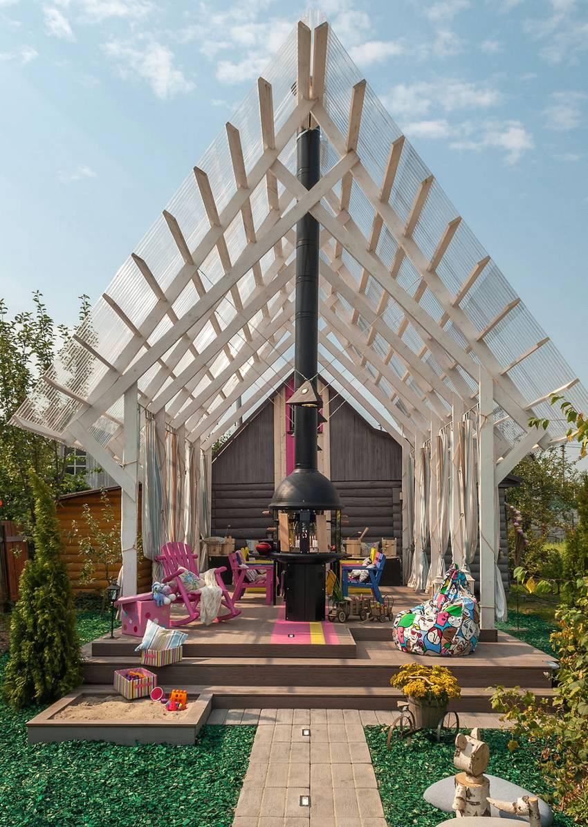 Необычный навес с двускатной крышей, пристроенный к деревянному дому