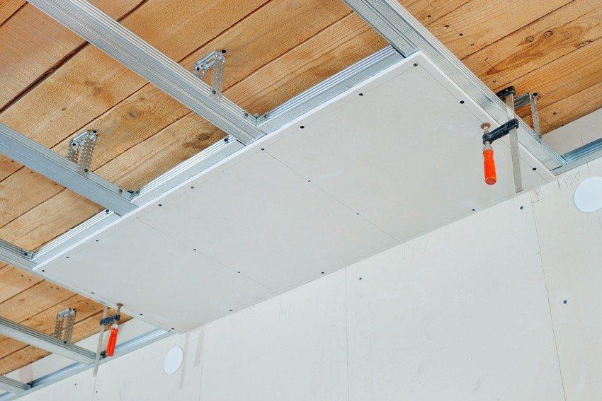 Монтаж гипсокартонного потолка в гостиной деревянного дома
