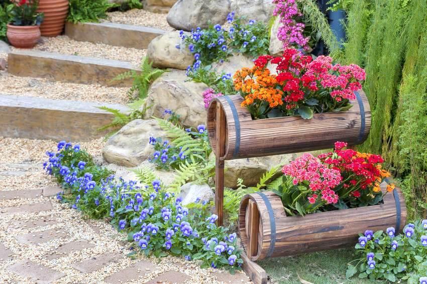 Пример устройства клумбы в деревянных бочонках