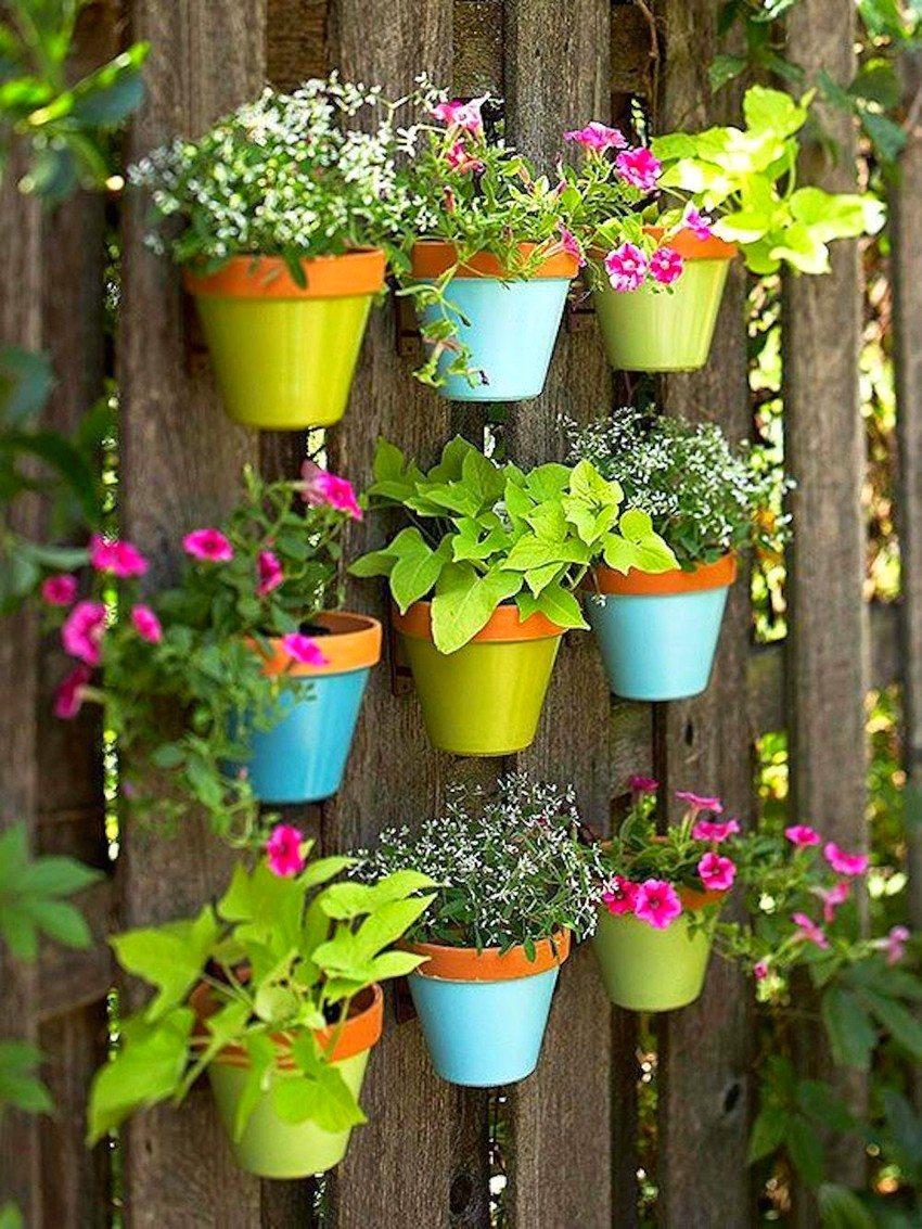 Вертикальная клумба из разноцветных горшков украшает деревянную изгородь