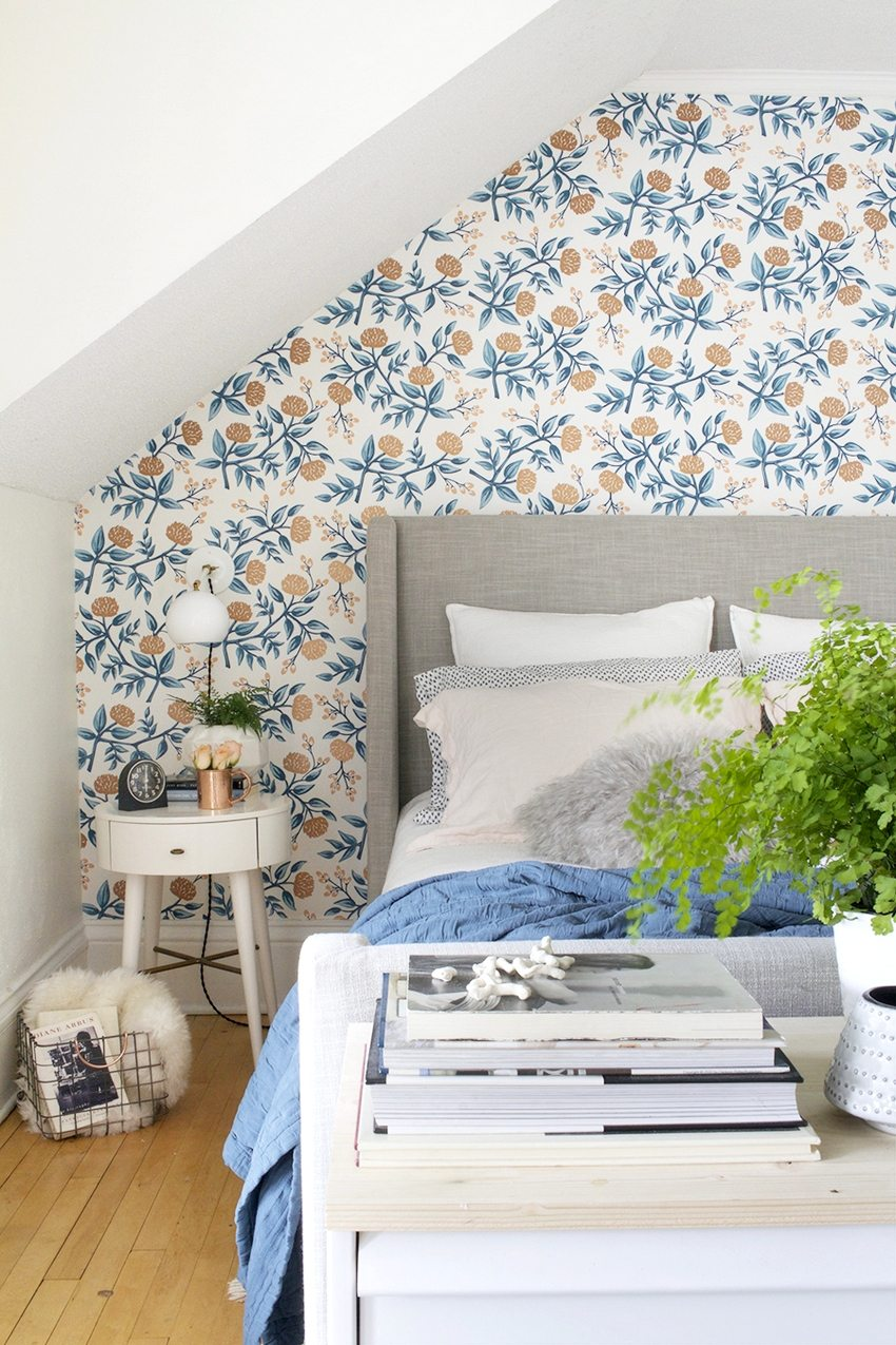The floral ornament in the bedroom design fits well with the monophonic walls