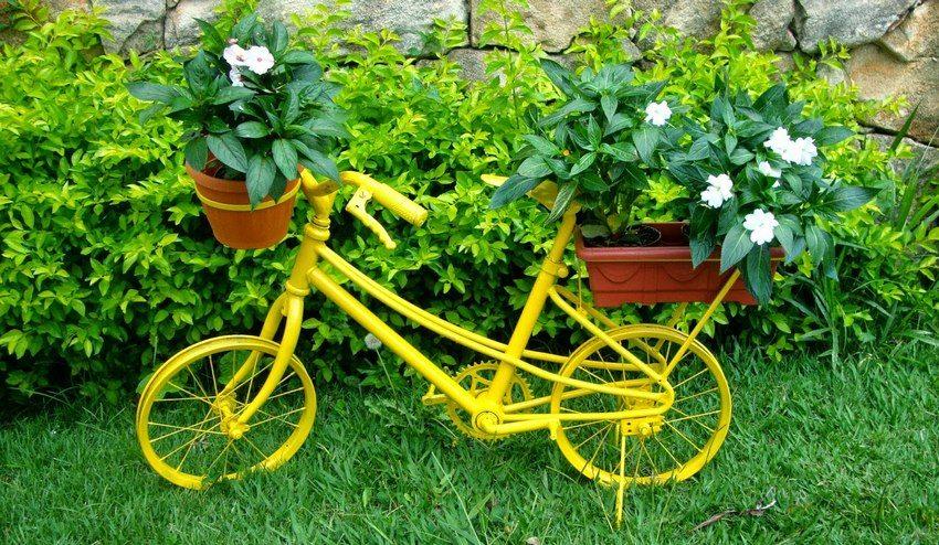 Старый велосипед, выкрашенный в яркий цвет, – отличный вариант для устройства цветника