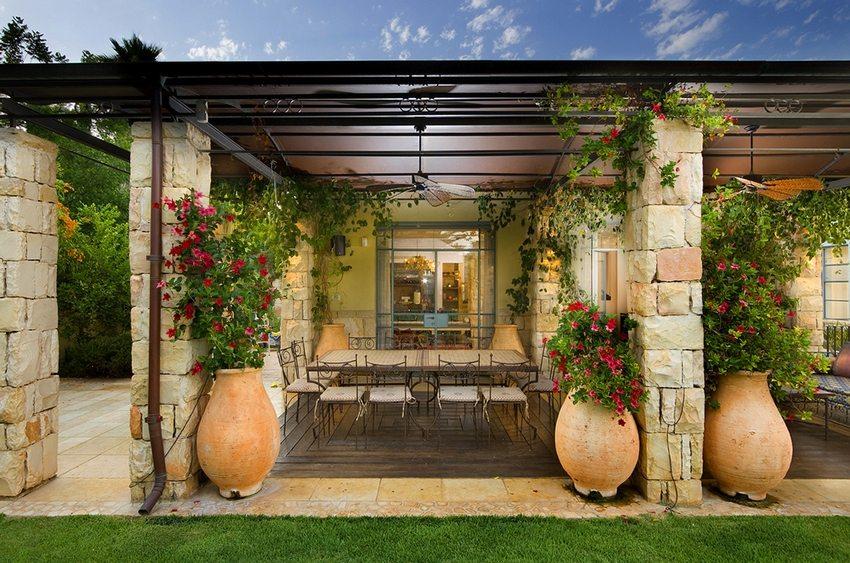 Вьющиеся растения и цветы в вазонах выступают в качестве элементов декора навеса