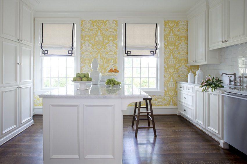Рисунок на желтых обоях красиво перекликается с белой кухней