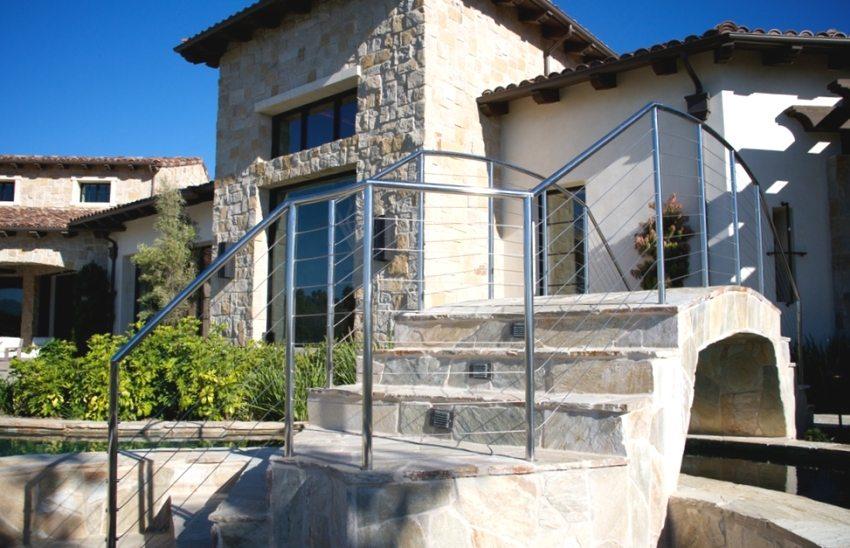 Каменный мостик во дворе частного дома украшают перила из нержавейки