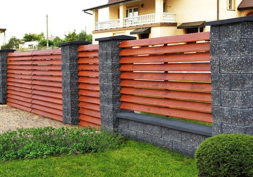 """Комбинированный забор, выполненный из дерева и камня. Доски расположены """"ёлочкой"""""""