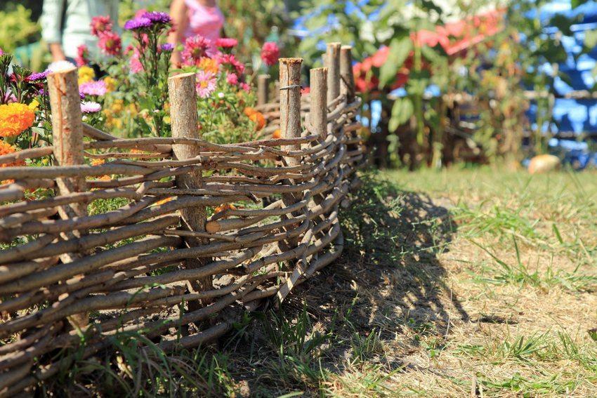 Изгородь с горизонтальным плетением обрамляет цветочную клумбу