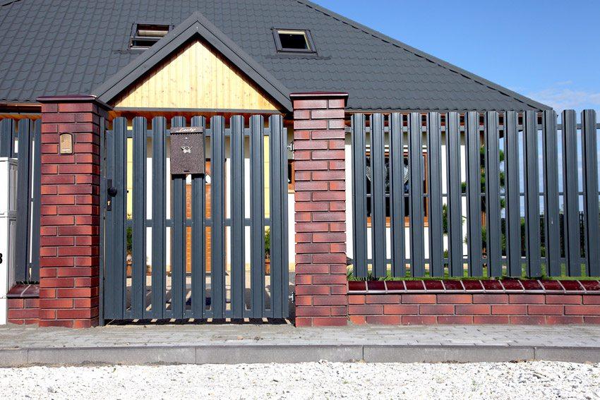 Забор из металлического штакетника с кирпичными столбами
