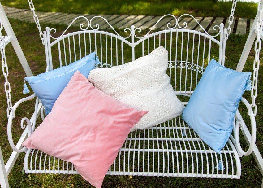 Невесомые на вид и изящные кованые качели с разноцветными подушками