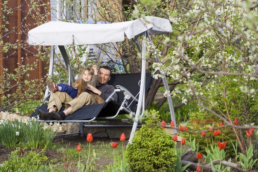 Металлические качели, расположенные в саду частного дома, станут излюбленным местом для отдыха