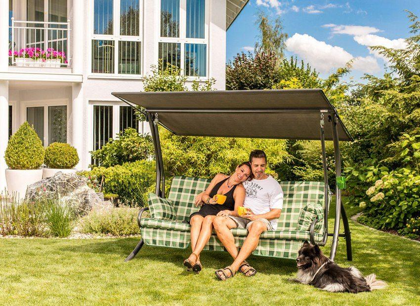 Металлические качели диванного типа с козырьком, установленные во дворе частного дома